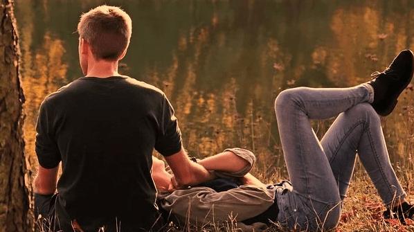 A husband and wife resting near a lake